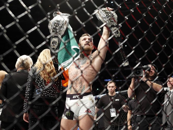 Conor+McGregor+shows+off+his+two+UFC+championship+belts+after+knocking+out+Eddie+Alvarez.