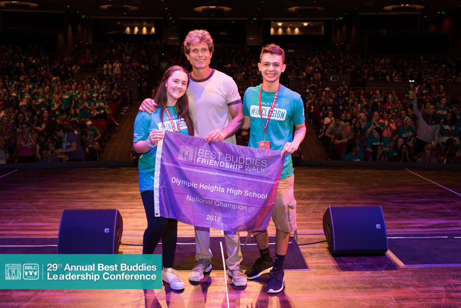 Olympic Heights Best Buddies Club officers Courtney Reiff (left) and Jacob Pasternack (right) accept a banner recognizing the OH chapter as the top fundraiser in the nation from Anthony Kennedy Shriver, Best Buddies International founder.