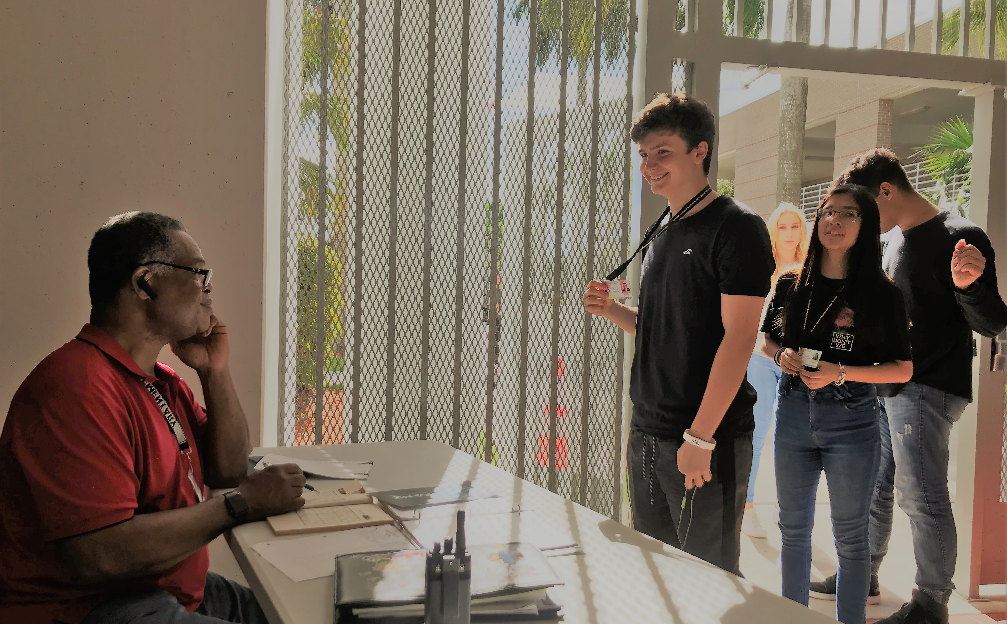 School security monitor Mr. Robert Police (seated) checks student ID badges of (from front to back) Hunter Moneck, Katelynn Dos Santos, Jose Simbaco, and Jenny Paul as they enter through the new security gate at the front entrance to the Olympic Heights campus.