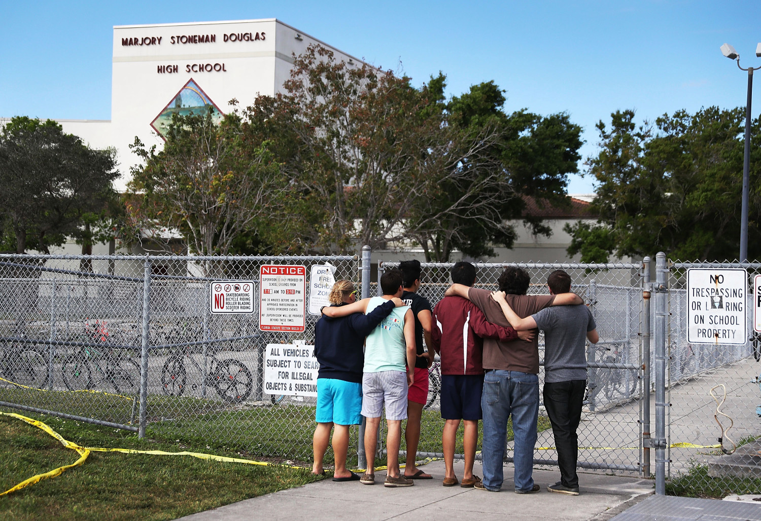 PARKLAND, FL - FEBRUARY 18:  People look on at the Marjory Stoneman Douglas High School on February 18, 2018 in Parkland, Florida. Police arrested 19 year old former student Nikolas Cruz for the mass shooting that killed 17 people on February 14.  (Photo by Joe Raedle/Getty Images)