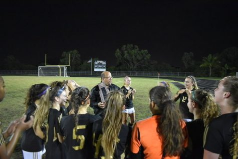 Soaking wet from the traditional championship dousing, Olympic Heights girls soccer head coach Jim Cappello addresses his team while holding the District 13-6A championship trophy.
