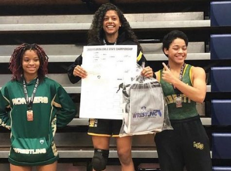 Olympic Heights wrestler Leidaly Rivera (center) on the medalist platform after winning her second consecutive state championship.