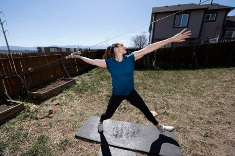 Kara Winger, a three-time Olympian and the U.S. national record holder in the javelin, uses a cable system to simulate throwing a javelin as she trains outside her home in Colorado Springs.
